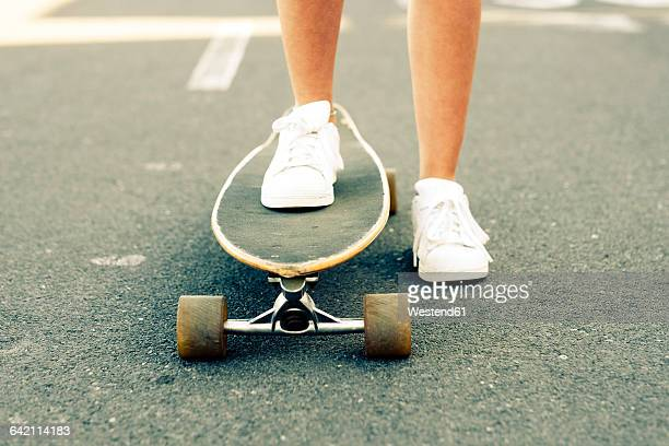 legs of teenage girl with longboard - desaturated stock pictures, royalty-free photos & images