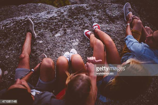 Legs of teenagers sitting outdoors together