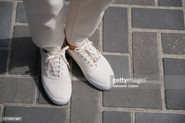 legs of the girl in new white sneakers and jeans. a woman in sports shoes standing on the pavement. fashionable and stylish lifestyle. - 西シベリア ストックフォトと画像