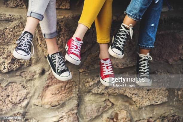 legs of three female teenager friends sitting cross-legged on a wall, wearing sneakers. - yellow shoe stock pictures, royalty-free photos & images