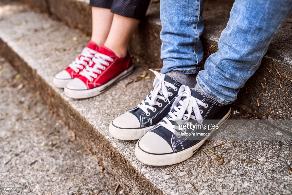 Legs of unrecognizable couple sitting on stairs. : Stock Photo