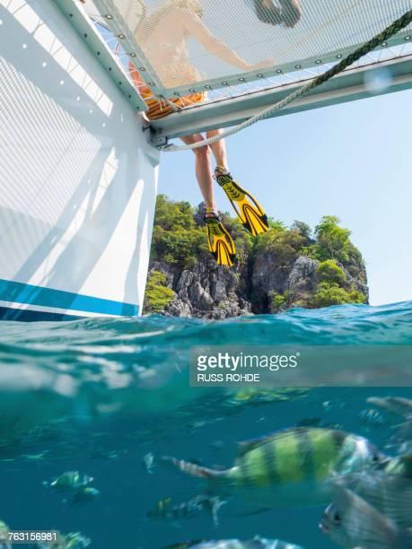 Legs of woman dangling from yacht, Koh Pak Ka, Krabi, Thailand, Asia