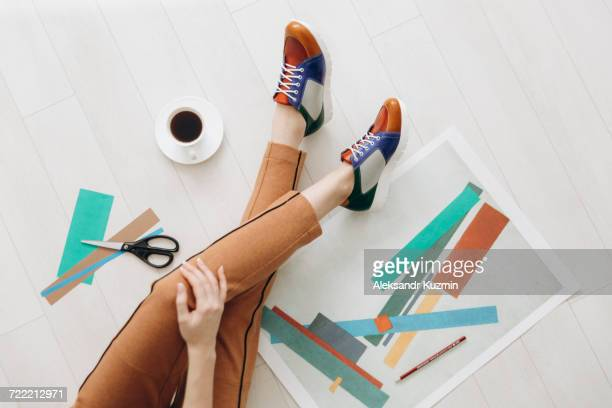 legs of woman designer sitting on floor wearing multicolor shoes - multi colored shoe stock pictures, royalty-free photos & images