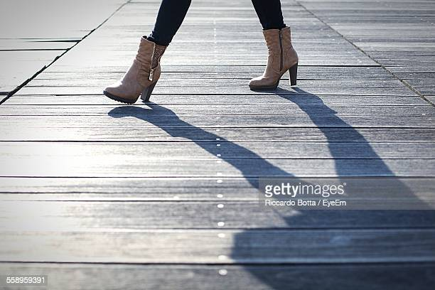 Legs Of Woman In Ankle Boots Walking On Boardwalk
