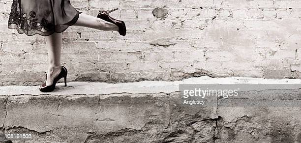 legs of woman in heels and skirt with brick background - standing on one leg stock pictures, royalty-free photos & images