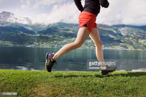 legs of woman jogging against sea and mountains - ランニングショートパンツ ストックフォトと画像