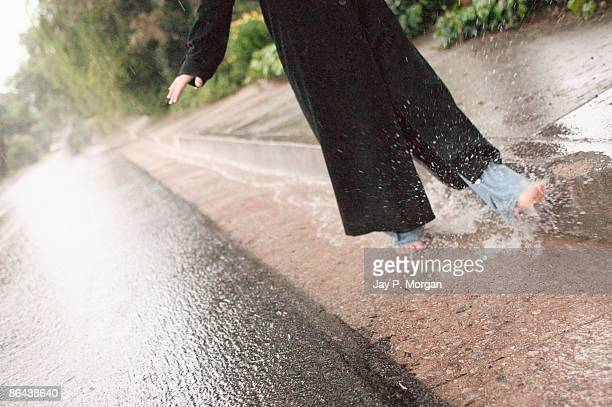 Legs of woman kicking water in gutter