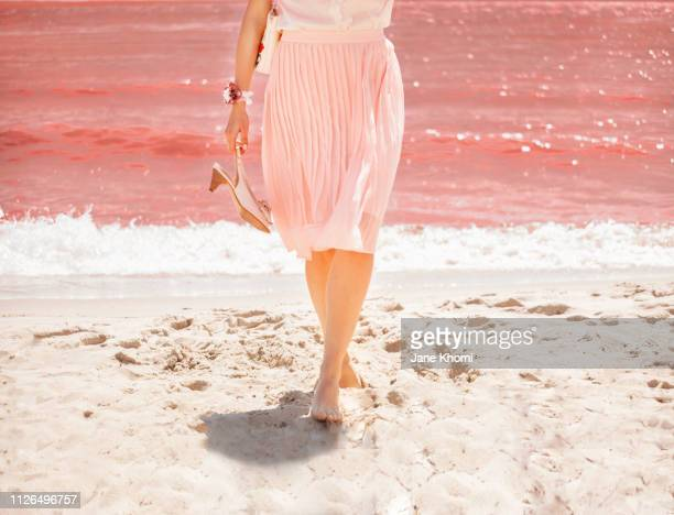 legs of woman on the living coral sea shore. - couleur corail photos et images de collection