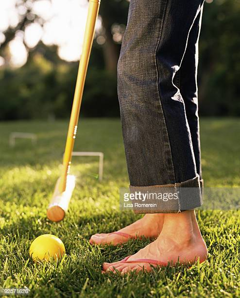 Legs of woman playing croquet