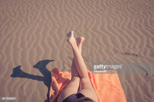 Legs of woman relaxing on the beach