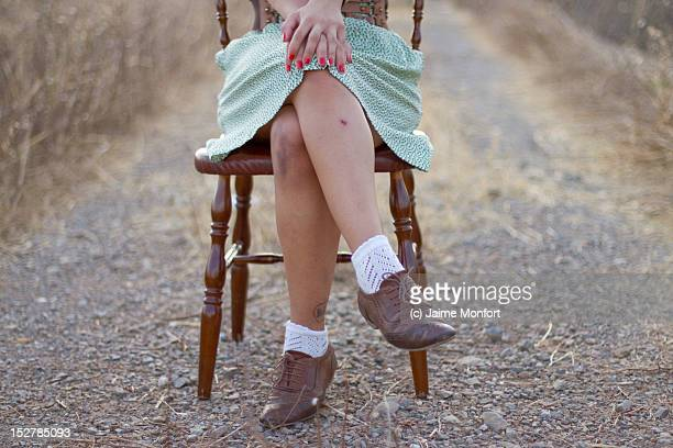 Legs of woman sitting on wooden chair