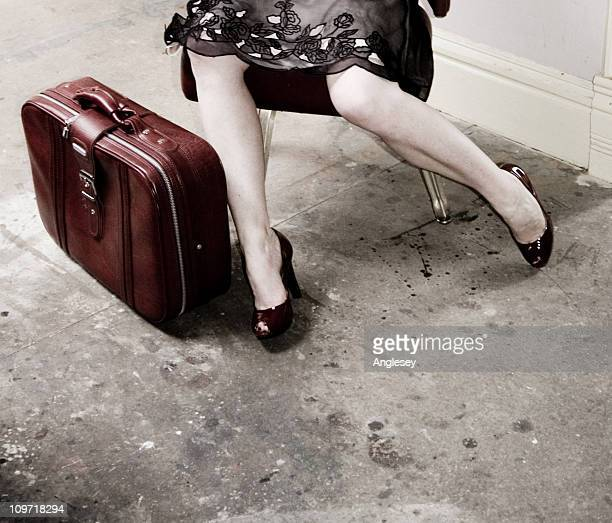 Legs of Woman Sitting Wearing Dress beside Red Vintage Suitcase