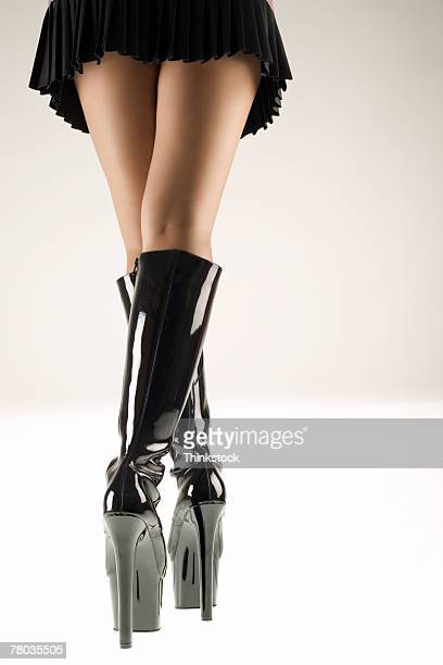 Legs of woman wearing miniskirt with stiletto boots