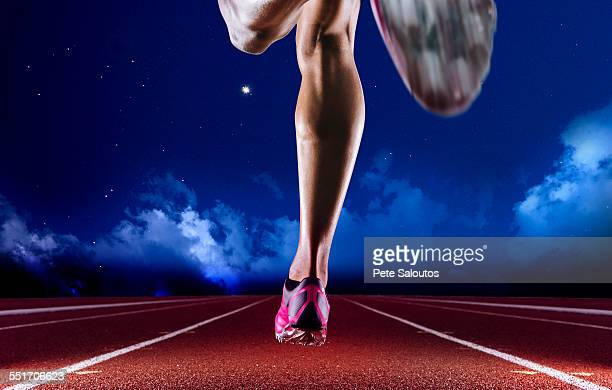 Legs of young female athlete running on race track at night