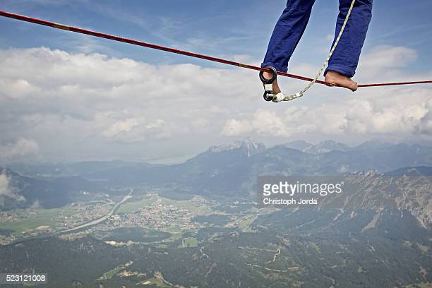Legs of young man balancing on high rope between two rocks in mountains, Alps, Tyrol, Austria