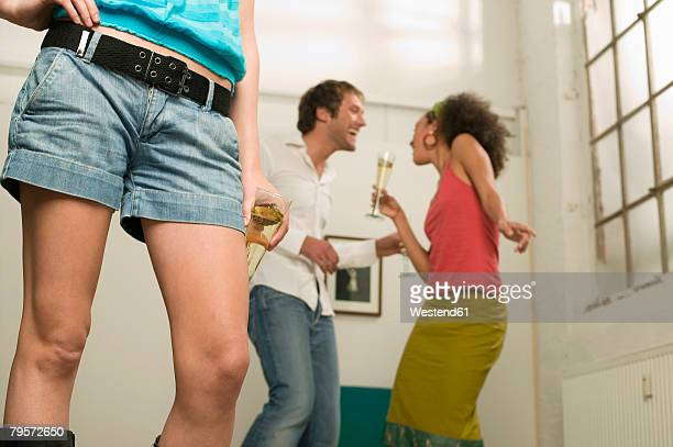 'Legs of young woman, couple dancing in background'