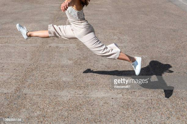 legs of young woman jumping on street during sunny day - legs apart stock pictures, royalty-free photos & images