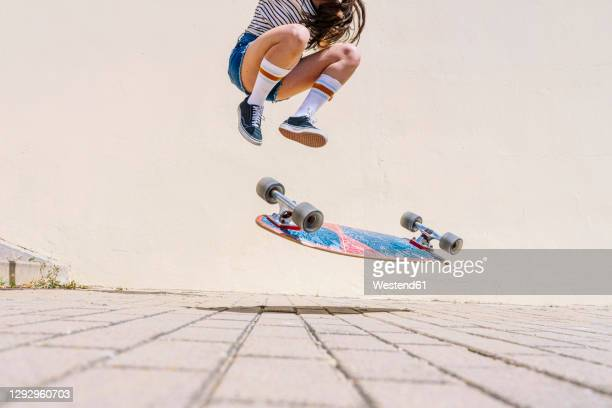 legs of young woman performing stunt on footpath against wall during sunny day - skating stock pictures, royalty-free photos & images