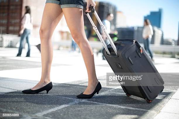 Legs of young woman walking with rolling suitcase