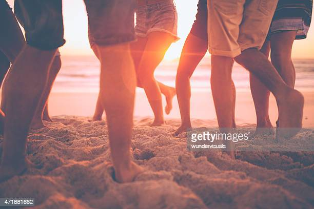Legs of youth dancing on the beach at sunset