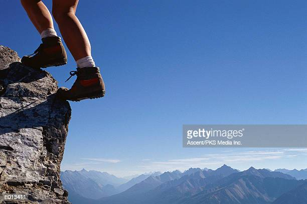 Legs on edge of cliff with mountains and sky beyond