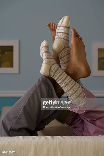 legs raised, intertwined - playing footsie stock photos and pictures