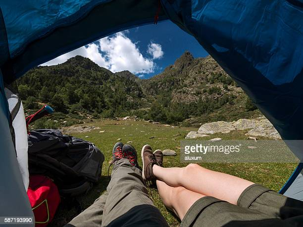 Legs sticking outside camping tent in the mountains