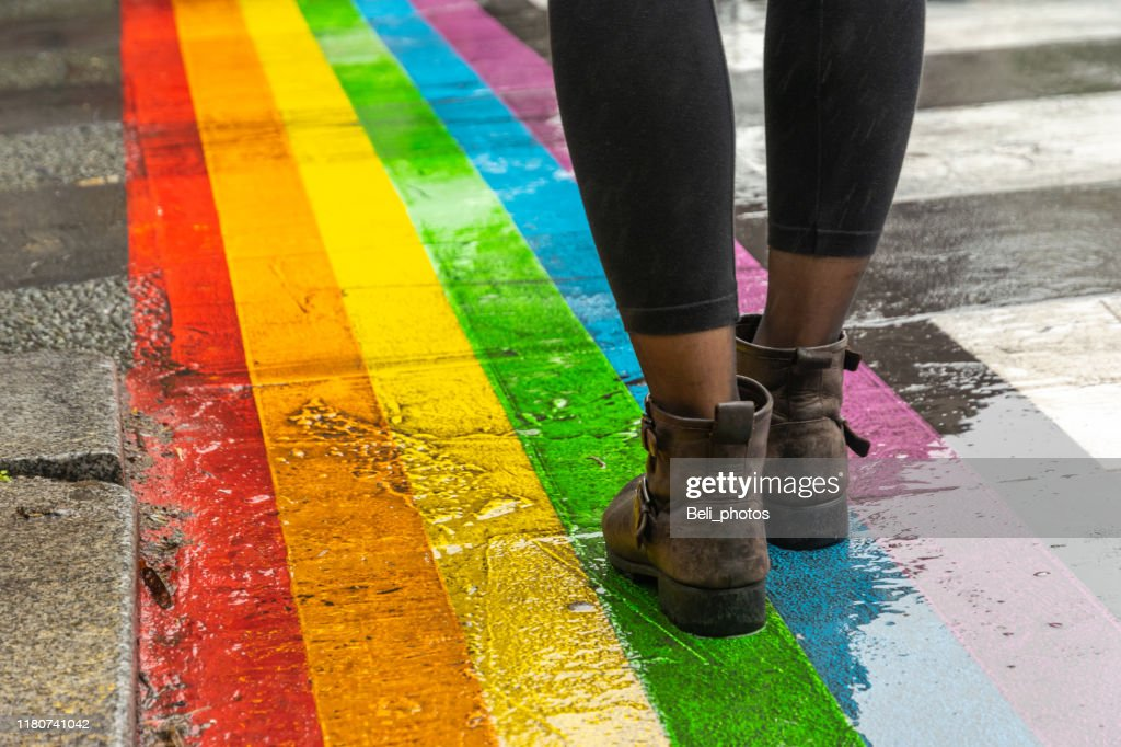 Legs walking on Gay rainbow crosswalk. : Stock Photo