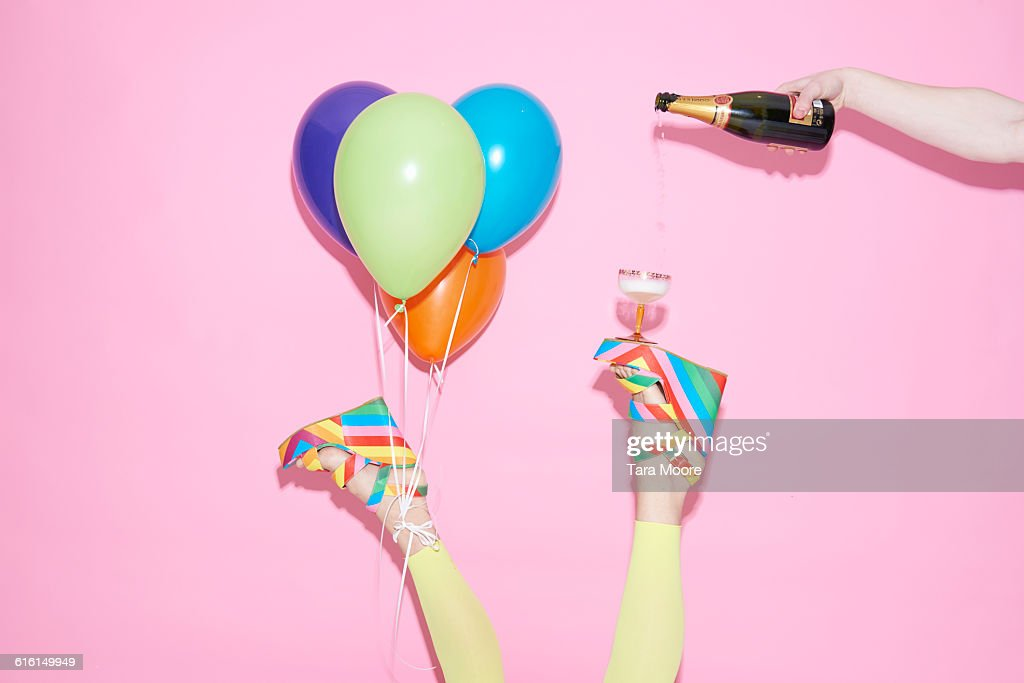 legs with champagne and balloons : Stock Photo
