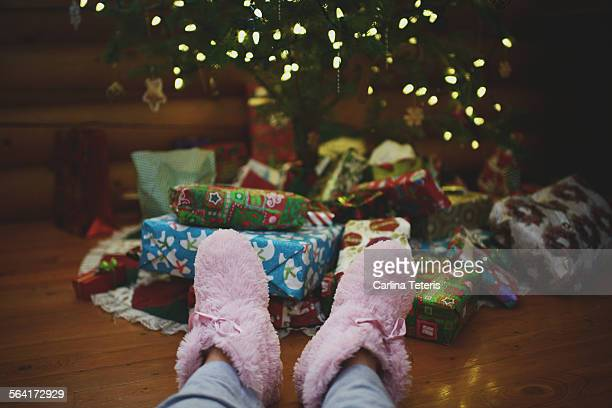 Legs with pink slippers in front of Christmas tree