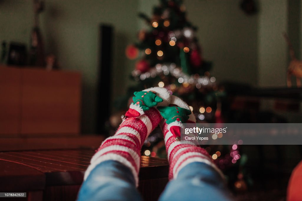 legs with xmas socks on table.Blurred xmas tree on background : Stock Photo