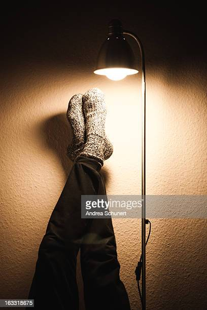 legs&feet leaning against a wall with shining lamp