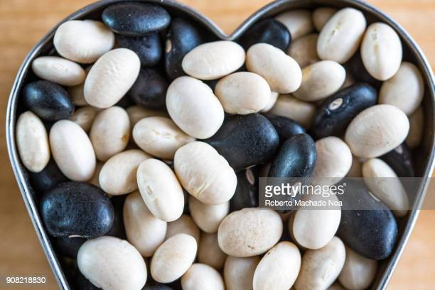 Legumes a mixture of black and white beans in a heart shape Health benefits of legumes include being an excellent source of vegetable protein