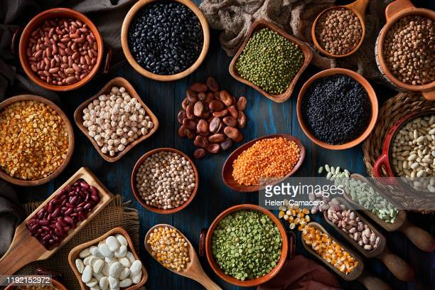 legumes and beans on a rustic wooden table - vegan food stock pictures, royalty-free photos & images