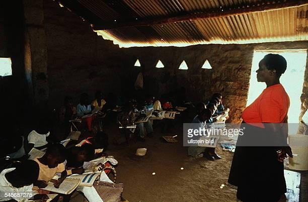 Lehrerin und Schulklasse mitSchreibheften beim Unterricht 00031995