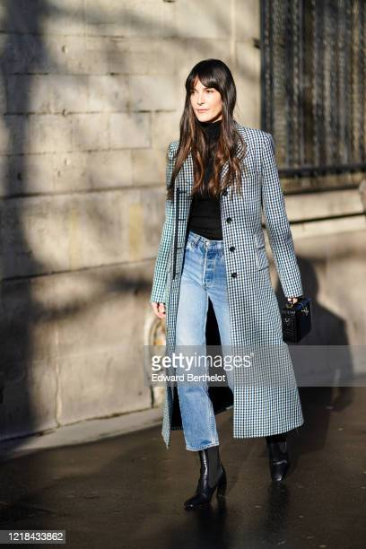 Leia Sfez wears a black and white checked long coat, a black crocodile pattern leather bag, a black turtleneck pullover, blue denim jeans pants,...