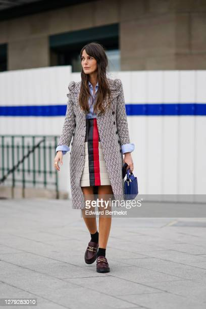 Leia Sfez wears a long gray coat with shoulder pads and printed geometric patterns, a blue shirt, a white black red padded leather skirt, a blue...