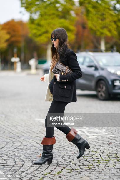Leia Sfez wears sunglasses, a black and white jacket, a black pullover, black pants, brown and black leather boots, a Chanel bag, outside Chanel,...