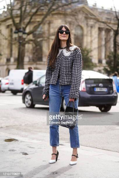 Leia Sfez wears sunglasses, a tweed checked pattern jacket with white embroidered collar, blue denim jeans, a Chanel bag, pointy shoes outside...
