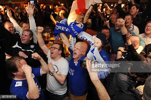 Leicester City Fans celebrate their team becoming Premier League champions as they watch Tottenham Hotspur play Chelsea at The Local Hero pub on...