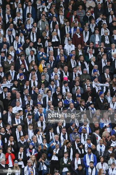Leicester City fans look on whilst wearing scarves in tribute to their chairman Vichai Srivaddhanaprabha during the Premier League match between...