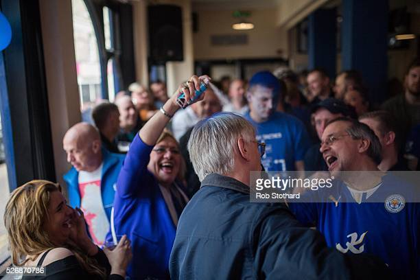 Leicester City fans watch as a fellow supporter has his hair coloured with blue spraypaint in The Market Tavern on May 1st 2016 in Leicester England...