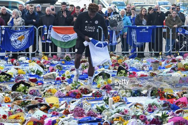 Leicester City youth team player Darnell Johnson lays a football shirt among floral tributes left to the victims of the helicopter crash which killed...