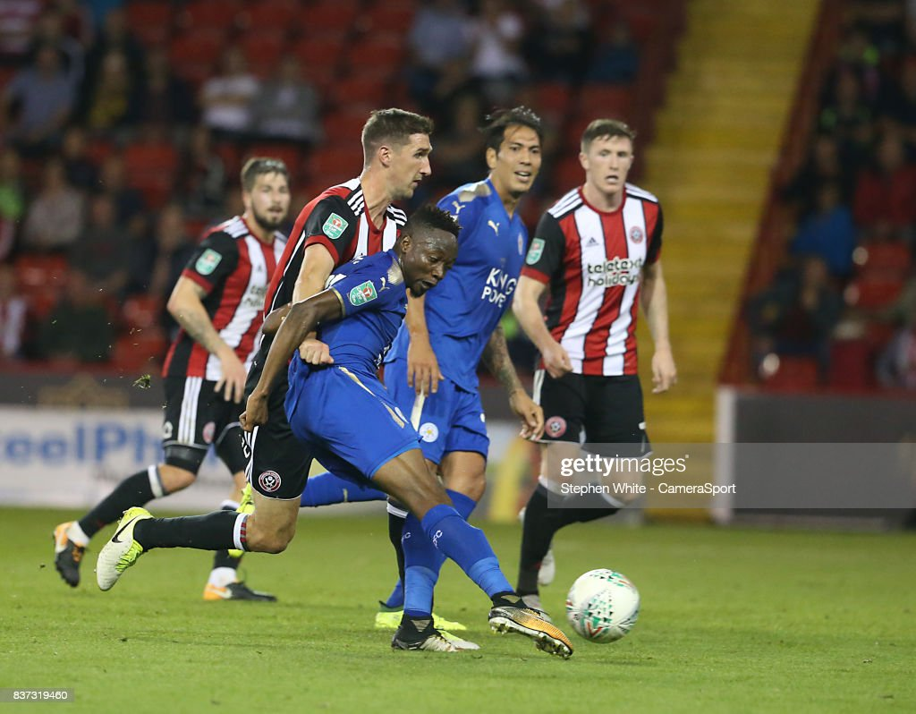 Leicester City's Ahmed Musa holds off the challenge from Sheffield United's Chris Basham and scores his side's fourth goal during the Carabao Cup Second Round match between Sheffield United and Leicester City at Bramall Lane on August 22, 2017 in Sheffield, England.
