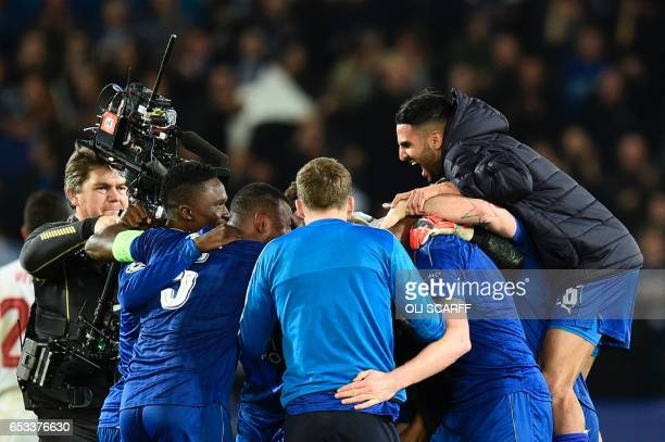 Leicester City's Algerian midfielder Riyad Mahrez jumps in to celebrate victory with his Leicester teammates at the end of the UEFA Champions League...