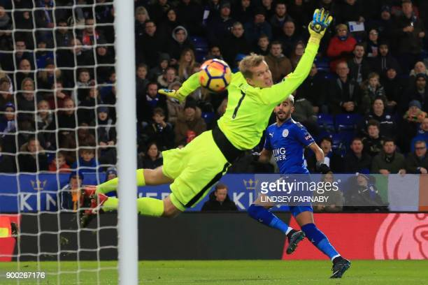 Leicester City's Algerian midfielder Riyad Mahrez scores the team's first goal past Huddersfield Town's Danish goalkeeper Jonas Lossl during the...