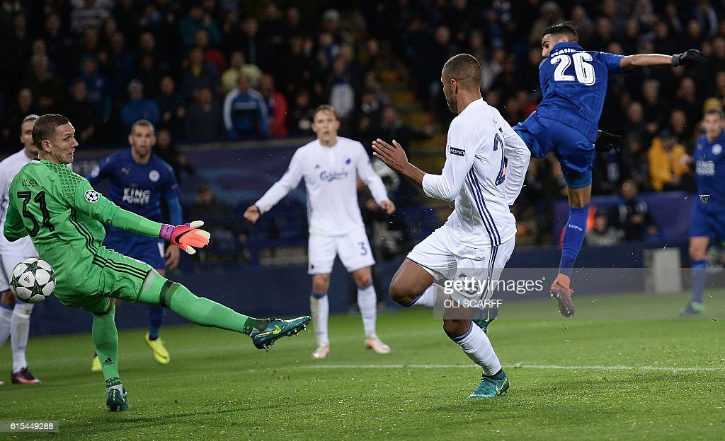 Leicester City's Algerian midfielder Riyad Mahrez (R) shoots past FC Copenhagen's Swedish goalkeeper Robin Olsen (L) to scores his team's first goal during the UEFA Champions League group G football match between Leicester City and FC Copenhagen at the King Power Stadium in Leicester, central England on October 18, 2016. / AFP / OLI