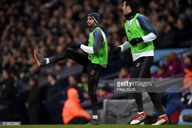 Leicester City's Algerian midfielder Riyad Mahrez warms up on the touchline during the English Premier League football match between Manchester City...