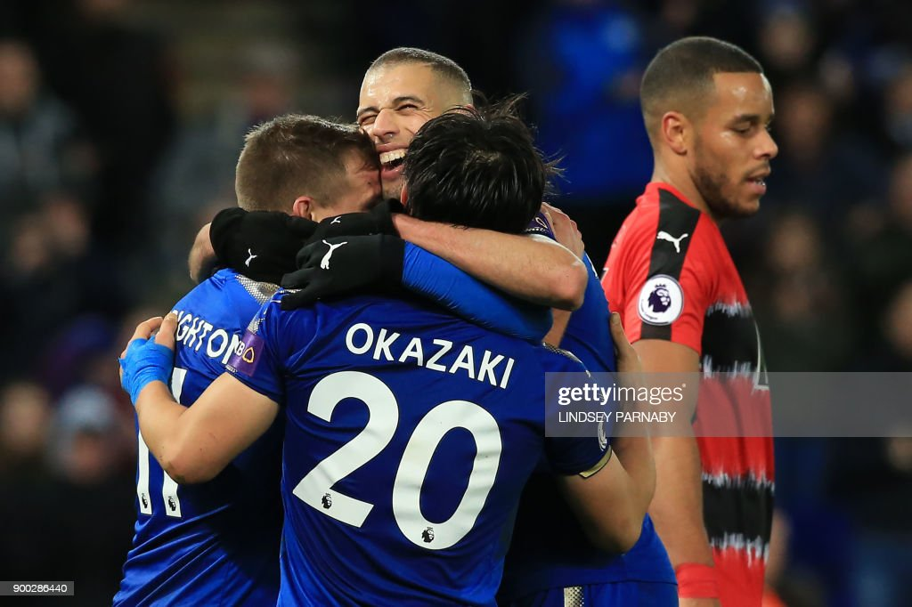 Leicester City's Algerian striker Islam Slimani (C) celebrates, with teammates, scoring the second goal during the English Premier League football match between Leicester City and Huddersfield Town at King Power Stadium in Leicester, central England on January 1, 2018. / AFP PHOTO / Lindsey PARNABY / RESTRICTED TO EDITORIAL USE. No use with unauthorized audio, video, data, fixture lists, club/league logos or 'live' services. Online in-match use limited to 75 images, no video emulation. No use in betting, games or single club/league/player publications. /