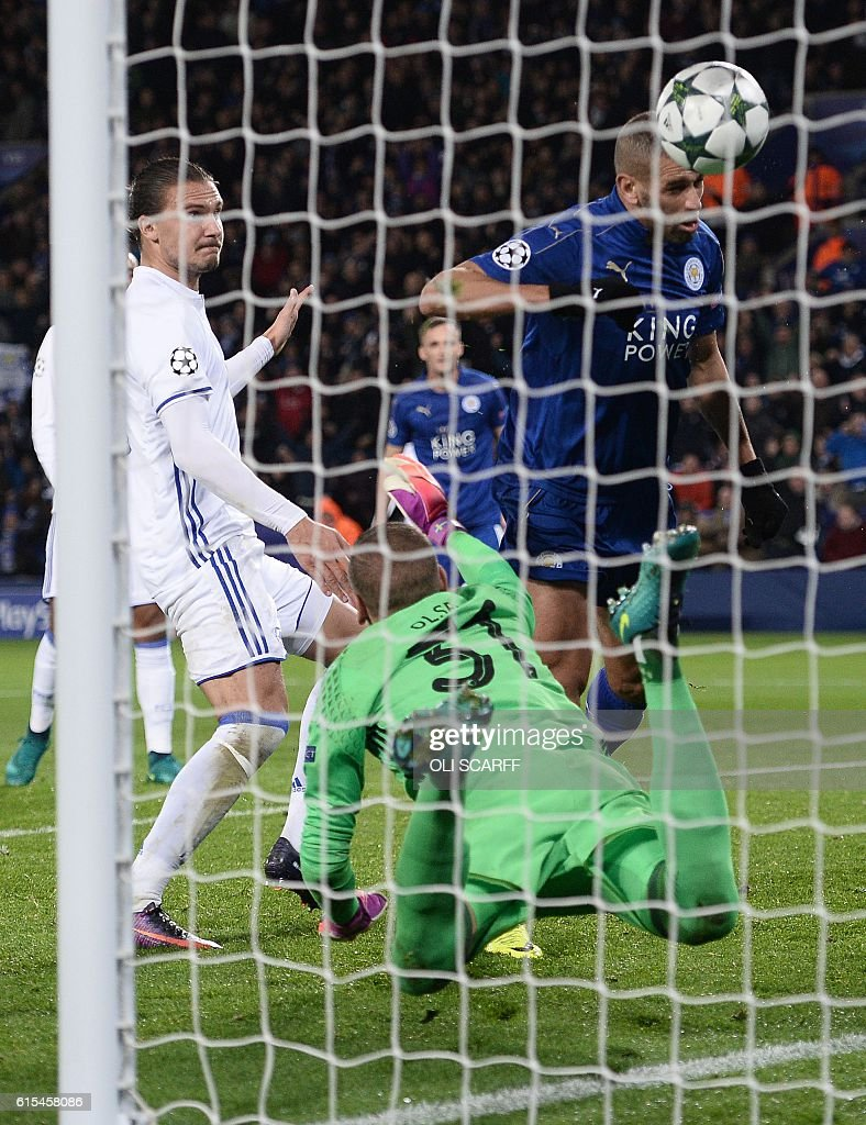 Leicester City's Algerian striker Islam Slimani (R) heads the ball to score past FC Copenhagen's Swedish goalkeeper Robin Olsen, but the goal is dissallowed as he was ruled to be offside, during the UEFA Champions League group G football match between Leicester City and FC Copenhagen at the King Power Stadium in Leicester, central England on October 18, 2016. / AFP / OLI